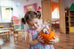 Cute little girl holding felt pumpkin toy. Vibrant background Stock Images
