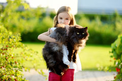 Cute little girl holding giant black cat Royalty Free Stock Images