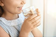 Cute little girl holding glass of fresh water at home