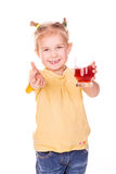 Cute little girl holding glass with juice smiling. With thumb up isolated on white Royalty Free Stock Photography