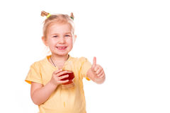Cute little girl holding glass with juice smiling with her thumb up. Isolated on white Royalty Free Stock Photo