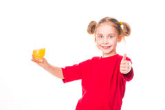Cute little girl holding glass with juice with thumb up. Cute little girl holding glass with juice smiling  with thumb up isolated on white Royalty Free Stock Photography
