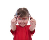 Cute little girl holding glasses and looking thru it Royalty Free Stock Photography