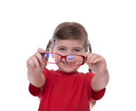 Cute little girl holding glasses and looking thru it Royalty Free Stock Photos