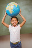 Cute little girl holding globe over head Royalty Free Stock Images