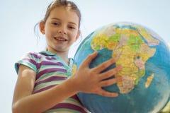 Cute little girl holding globe Stock Photos