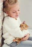 Cute little girl holding hands on the ginger kitten Stock Photos