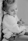 Cute little girl holding hands on the ginger kitten Stock Photo