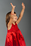 Cute little girl holding hands up. Cute four-year-old girl in a red dress holding her hands up and smiling Royalty Free Stock Photos