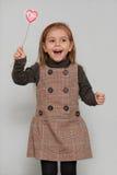 Cute little girl holding heart shape. Portrait of little girl holding heart shape Stock Image
