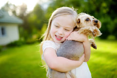 Cute little girl holding her funny yorkshire terrier dog royalty free stock images