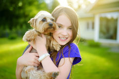 Cute little girl holding her funny yorkshire terrier dog Stock Images