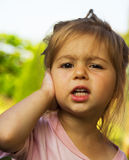Cute little girl holding her hand at the ear Stock Photos