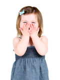 Cute little girl holding her hands over her mouth stock image