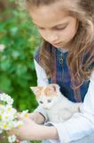 Cute little girl holding kitty and a bouquet of daisy flowers on her hands royalty free stock image