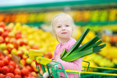 Cute little girl holding a leek in a food store Royalty Free Stock Image