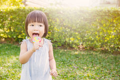 Cute little girl holding the lollipop in the par Royalty Free Stock Photos