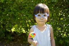 Cute little girl holding the lollipop in the park Royalty Free Stock Photos