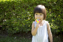 Cute little girl holding the lollipop in the park Royalty Free Stock Images