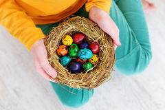 Cute little girl holding a nest with colored Easter eggs at home on Easter day. Celebrating Easter at spring Stock Images