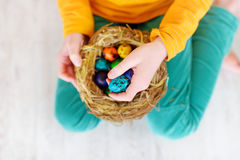 Cute little girl holding a nest with colored Easter eggs at home on Easter day. Celebrating Easter at spring Royalty Free Stock Photo