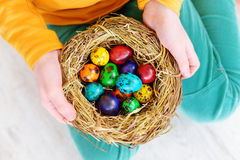 Cute little girl holding a nest with colored Easter eggs at home on Easter day. Celebrating Easter at spring Stock Image