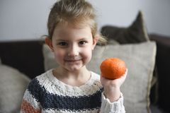 Cute little girl holding orange royalty free stock photography