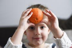 Cute little girl holding orange stock images