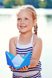 Cute little girl holding origami boat outdoors Royalty Free Stock Photos