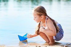 Cute little girl holding origami boat outdoors Stock Photos