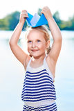 Cute little girl holding origami boat outdoors Stock Photo