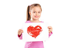 Cute little girl holding a painting of a red heart Royalty Free Stock Photos