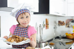 Cute little girl holding plate with cookies Stock Photos