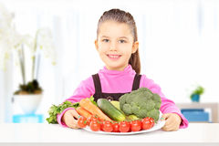 Cute little girl holding a plate full of vegetables Stock Image