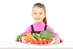 Cute little girl holding a plate full of vegetables Royalty Free Stock Images
