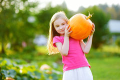 Cute little girl holding a pumpkin Stock Image