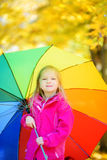 Cute little girl holding rainbow umbrella on beautiful autumn day. Happy child playing in autumn park. Stock Image