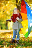 Cute little girl holding rainbow umbrella on beautiful autumn day. Happy child playing in autumn park. Stock Images