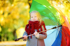 Cute little girl holding rainbow umbrella on beautiful autumn day. Happy child playing in autumn park. Royalty Free Stock Photo