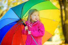 Cute little girl holding rainbow umbrella on beautiful autumn day. Happy child playing in autumn park. Stock Photography