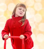 Cute little girl holding a red pen from the cart. Stock Image