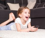Little girl watching TV. Cute little girl holding a remote control Stock Images