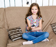 Cute little girl holding a remote control Stock Photography