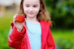 Cute little girl holding a ripe strawberry Stock Images