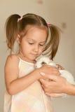 Little girl holding small rabbit Stock Photos