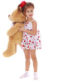 Cute little girl holding a teddy bear arms. Isolated on white Stock Image