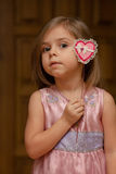 Cute little girl holding up a heart shape. Portrait of cute little girl holding up heart shape Royalty Free Stock Images