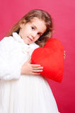 Cute little girl holding valentine's heart on red Stock Photography