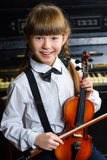Cute little girl holding a violin indoor Stock Image