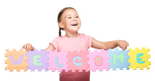 Cute little girl is holding Welcome slogan Stock Photo